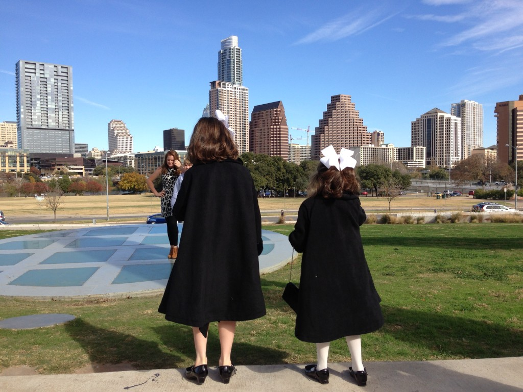 Our girls dressed in their fancy coats for the Nutcracker Ballet, looking out over the Austin Skyline